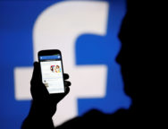 A man is silhouetted against a video screen with a Facebook logo as he poses with a smartphone in this photo illustration taken in Zenica