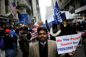A supporter of U.S. President-elect Donald Trump walks away from a protest near Trump Tower in the Manhattan borough of New York