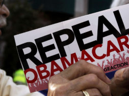 "File photo of a demonstrator holding a pamphlet outside a ""Defund Obamacare Tour"" rally in Indianapolis"