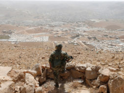 FILE PHOTO: A Lebanese soldier carries his weapon as he stands at an army post in the hills above the Lebanese town of Arsal, near the border with Syria