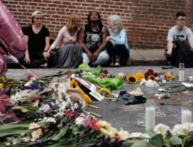 Women sit by an impromptu memorial of flowers at the scene of the car attack on a group of counter-protesters in Charlottesville