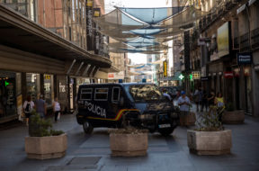 A police van drives by pots placed to prevent possible attacks on a pedestrian street in the center of Madrid