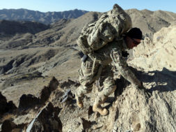 FILE PHOTO: US soldier climbs a hill near the town of Walli Was in Paktika province