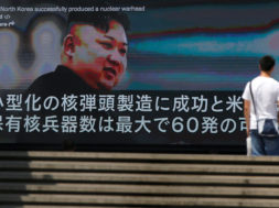 A passerby walks past a street monitor showing news of North Korea's fresh threat in Tokyo