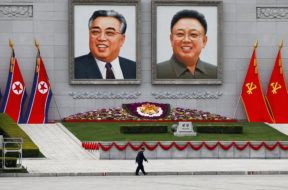 FILE PHOTO: A man walks in front of portraits of North Korea founder Kim Il Sung and late leader Kim Jong Il in central Pyongyang