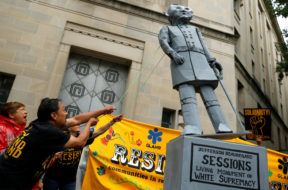 Immigration activists pull down a statue of U.S. Attorney General Jeff Sessions