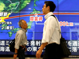 Passersby in Tokyo walk in front of a TV screen reporting news about North Korea's missile launch