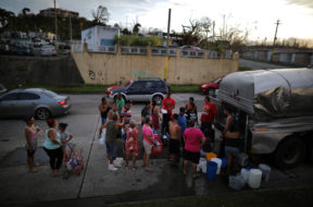 Local residents wait in line during a water distribution in Bayamon following damages caused by Hurricane Maria in Carolina, Puerto Rico