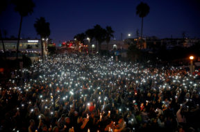 People hold candles and flashlights into the air during a memorial for Rachael Parker and Sandy Casey, Manhattan Beach city employees and victims of the October 1st Las Vegas Route 91 music festival mass shooting