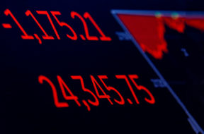 A screen displays the Dow Jones Industrial Average following the closing bell on the floor